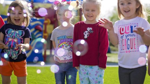 young girls playing with bubbles outside